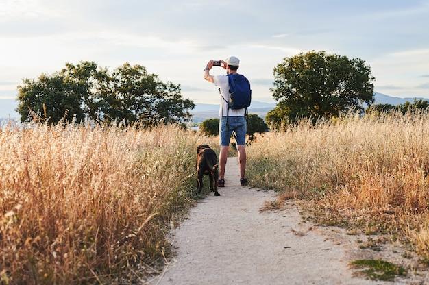 Вид сзади человека с рюкзаком, фотографирующего со своей собакой на прогулке в сельской местности на закате