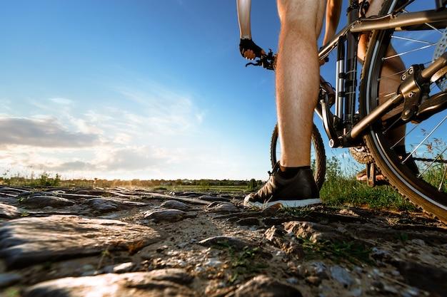 Вид сзади человека с велосипедом против голубого неба.