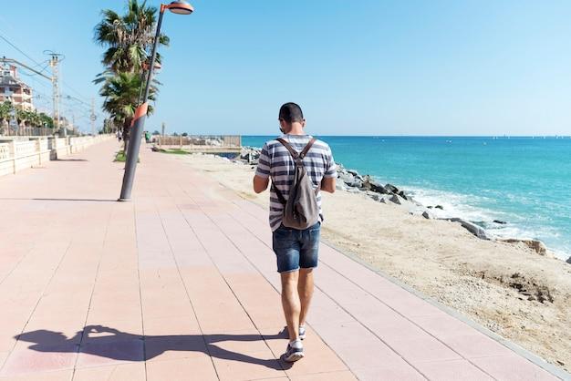 晴れた日に海岸の隣の遊歩道を歩いてバックパックを持つ男の背面図