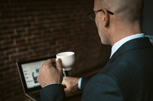 Вид сзади зрелого делового человека в деловом костюме, держащего чашку кофе, сидя за столом