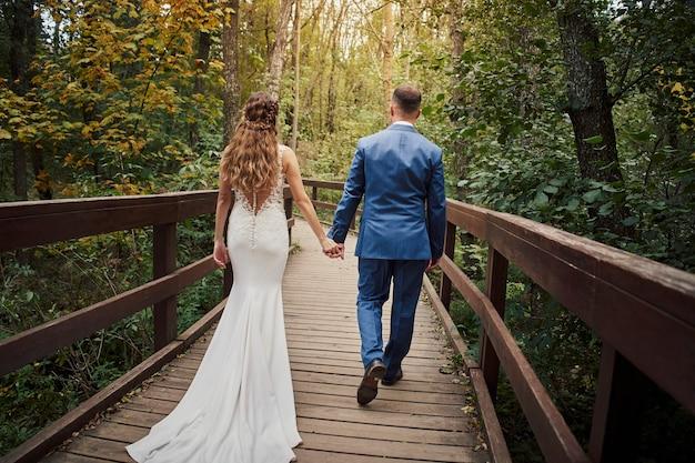 森の橋を歩いている新婚夫婦の背面図