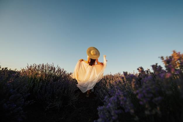 柔らかいバラの長いドレスを着たかわいい少女の背面図