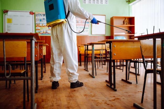 학년이 시작되기 전에 교실을 소독하는 전문 위생 작업자의 뒷모습. 방호복을 입은 남성이 코로나바이러스 코비드-19로부터 강당을 청소하고 있습니다. 보건 의료.