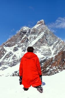 Вид сзади лыжника, смотрящего на снежно-белый горный пейзаж вокруг