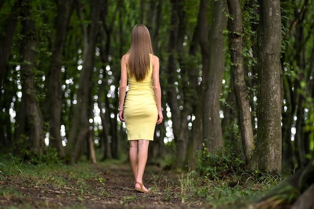 우울한 어두운 숲에 서 있는 노란 드레스를 입은 날씬한 여성의 뒷모습.