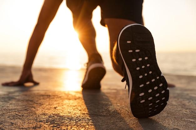 走る準備をしているスポーツマンの背面図