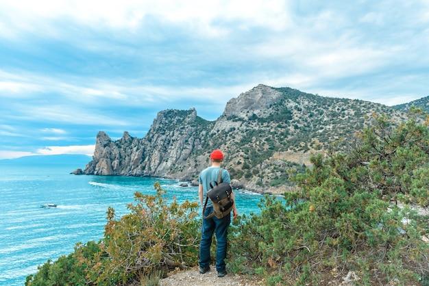 여행에서 바다에 배낭을 메고 있는 관광 남자의 뒷모습. 여행 컨셉