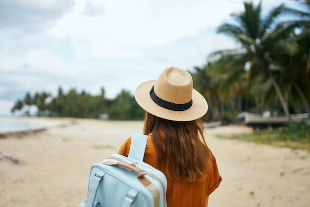 島のバックパックを持つ旅行者の背面図