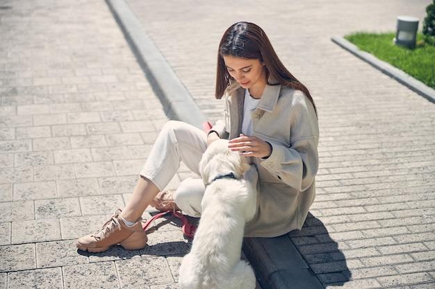 彼の右足で若い白人女性に触れている白い犬の背面図