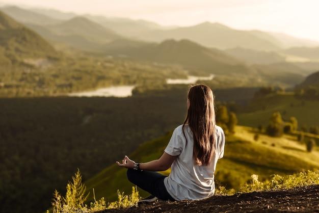 Вид сзади на женщину-путешественницу, сидящую и медитирующую на вершине горы во время заката с видом на реку