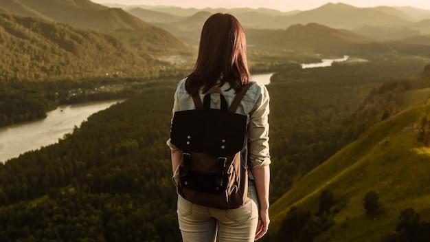 배낭 여성 등산객의 뒷면은 휴가 여행에서 일출 산에서 산 강을 본다. 여행 및 모험 개념