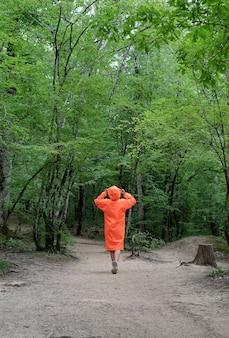 森の中を歩いているオレンジ色のレインコートを着た女性の背面図。アクティブなライフスタイルと旅行