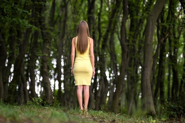 Вид сзади женщины в желтом платье, стоящей в угрюмом темном лесу.