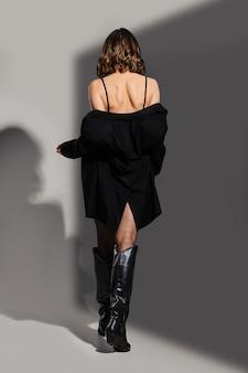 スタジオで革の乗馬ブーツでブレザーを脱いでいる女性の背面図