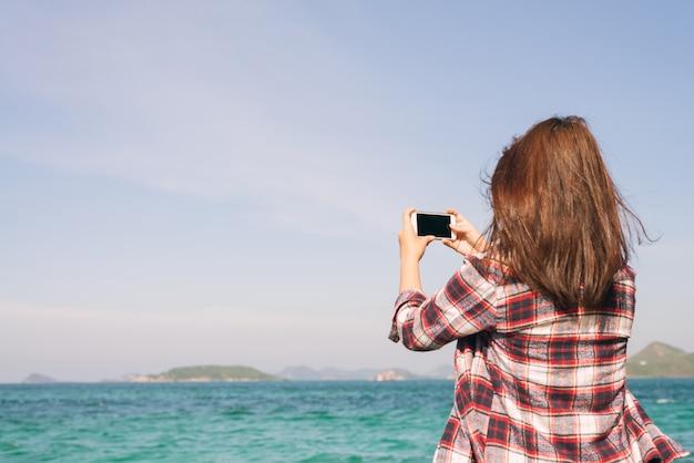 Вид сзади женщина с фотографией с помощью смарт-телефона на горизонте на пляже.