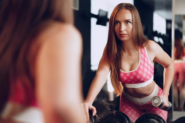 Вид сзади женщины, тренирующей руки с гантелями в тренажерном зале