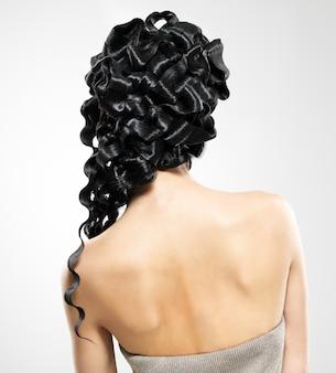 ファショインスタイルの巻き毛のヘアスタイルのポーズを持つ女性の背面図