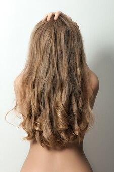 長いブロンドの髪を持つ女性の背面図