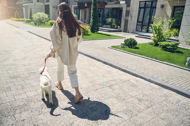ペットを散歩に連れて行く緩い長い髪の女性の背面図