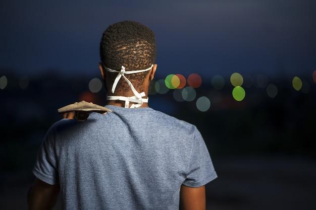 シャベルを保持している保護フェイスマスクで若いアフリカ系アメリカ人男性の背面図