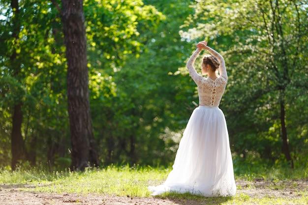 Вид сзади молодой невесты с поднятыми руками на фоне красивой растительности