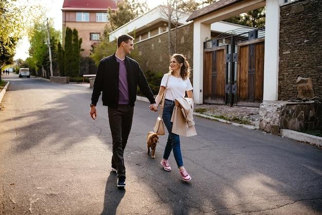 Вид сзади молодой пары, выгуливающей собаку на улице города