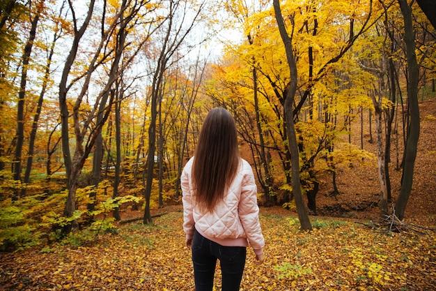 秋の公園で若い女性の背面図