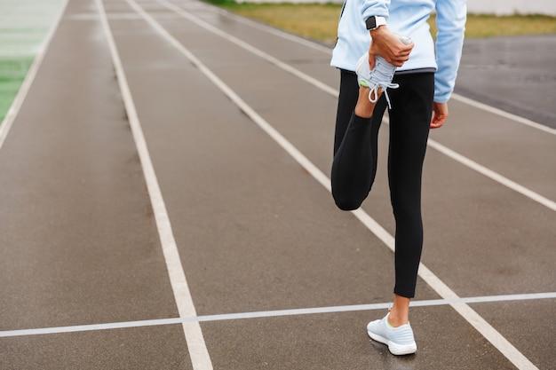 경기장에서 스트레칭 운동을 하는 젊은 아프리카 스포츠 여성의 뒷모습