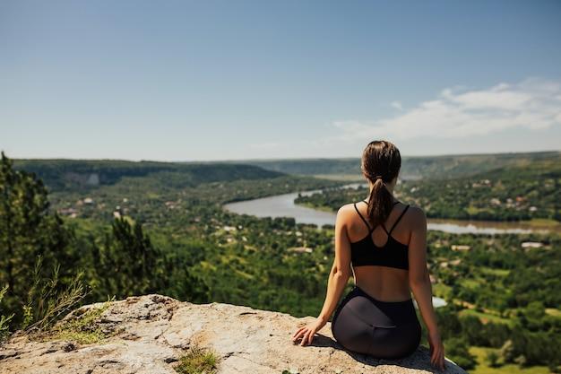 岩の上に座って、川と町のパノラマで遠くを見ているスポーツウェアの少女の背面図