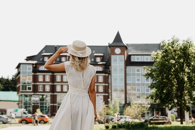 Вид сзади молодой счастливой женщины в соломенной шляпе в европейском городе. модная женщина-путешественница на незнакомой улице во время летнего приключения