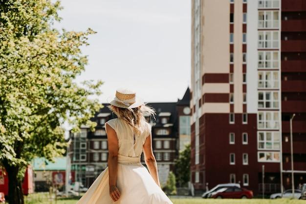 Вид сзади молодой счастливой женщины в соломенной шляпе в европейском городе.
