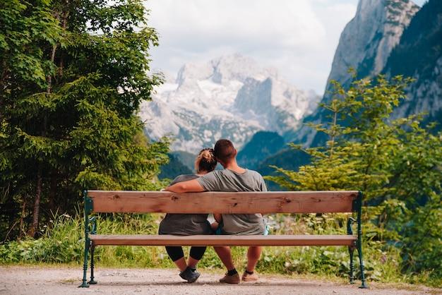 夏に、オーストリアの山々を見ているベンチ公園に座っている若いラテンカップルの背面図。
