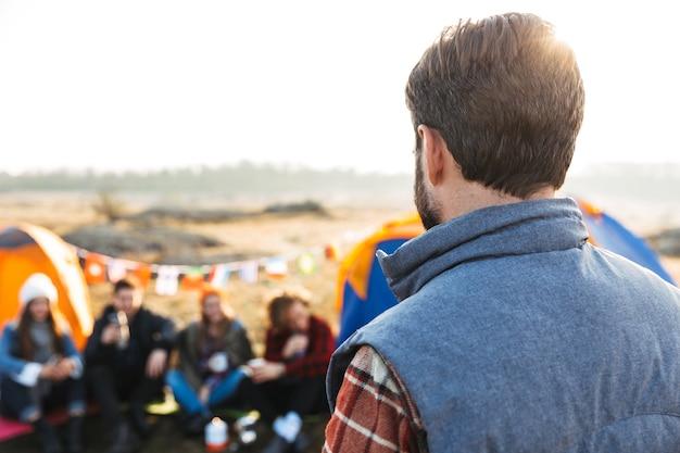 彼の友人とキャンプ場に立っている若い男の背面図
