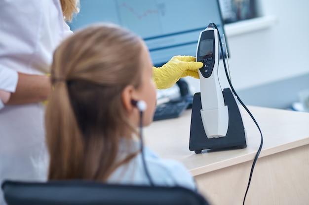 Вид сзади молодого пациента, сидящего во время аудиометрического теста, проводимого квалифицированным врачом