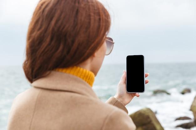 Вид сзади молодой рыжей женщины в осеннем пальто, гуляющей по пляжу, с пустым экраном мобильного телефона