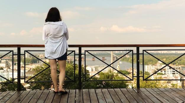Вид сзади молодой женщины в белой рубашке, брюнетка-путешественница смотрит на городской пейзаж в солнечный день с высокого холма со смотровой площадкой для туристов. винтаж.