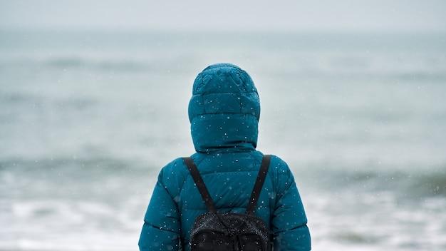 Вид сзади молодой женщины в зеленом пуховике и с черным рюкзаком, стоящей на песчаном пляже на фоне морского горизонта
