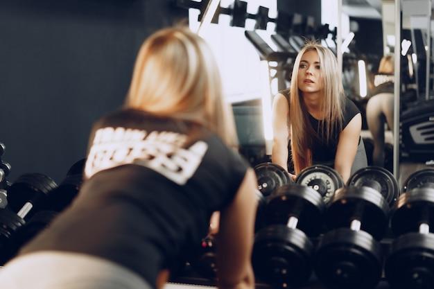 ジムでダンベルで彼女の手を訓練する若い女性の背面図