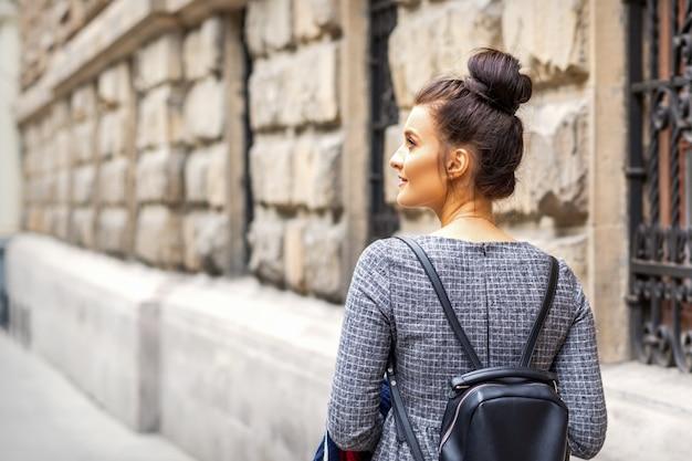 배낭을 가진 젊은 여자의 뒷모습은 유럽 도시에서 산책