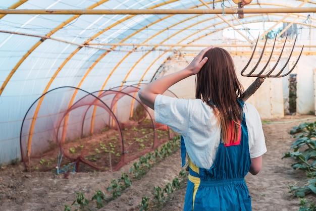 草の熊手ツールを持つ若い女性の背面図