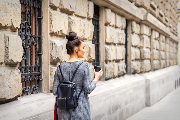 Вид сзади молодой женщины с горячим напитком и рюкзаком гуляет по европейскому городу
