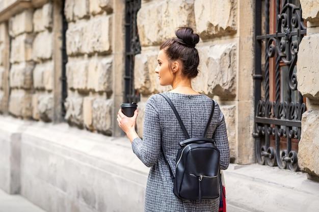 뜨거운 음료와 배낭을 가진 젊은 여성의 뒷모습이 유럽 도시에서 산책