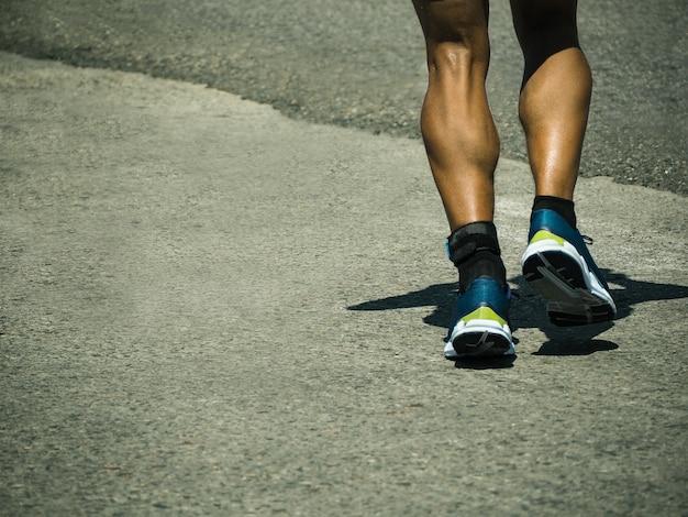 복사 공간 배경으로 아스팔트 도로를 달리는 활동적인 남자의 뒷모습