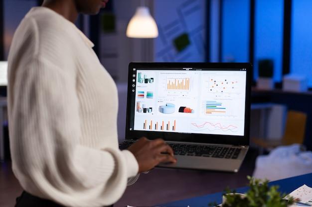 늦은 밤에 노트북을 들고 재무 통계를 분석하는 아프리카 사업가의 뒷모습