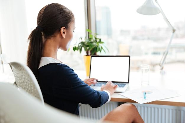 ノートパソコンとオフィスのテーブルのそばに座ってドレスを着てアフリカのビジネス女性の背面図