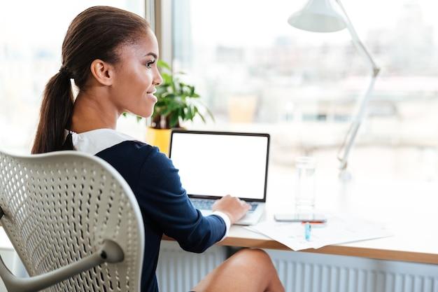 ラップトップと脇を見てオフィスの窓の近くのテーブルのそばに座ってドレスを着たアフリカのビジネス女性の背面図