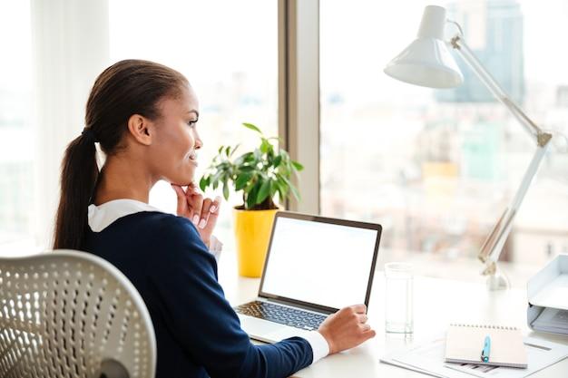 窓の近くの職場に座って、オフィスでラップトップを使用してドレスを着てアフリカのビジネス女性の背面図