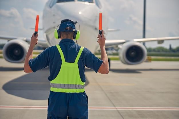 コックピットの乗組員に前進信号を送る航空機労働者の背面図
