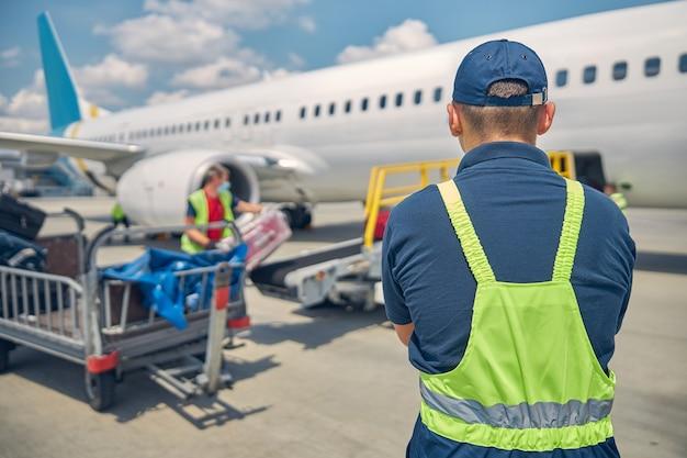 Вид сзади на работника аэропорта, который контролирует загрузку багажа на конвейерную ленту