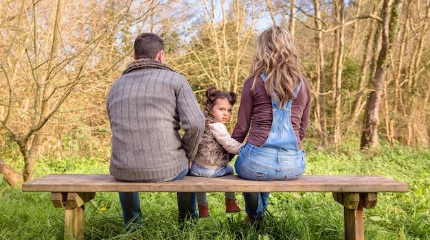 Вид сзади сердитой маленькой девочки, смотрящей в камеру между мужчиной и женщиной, сидящими на деревянной скамейке в парке